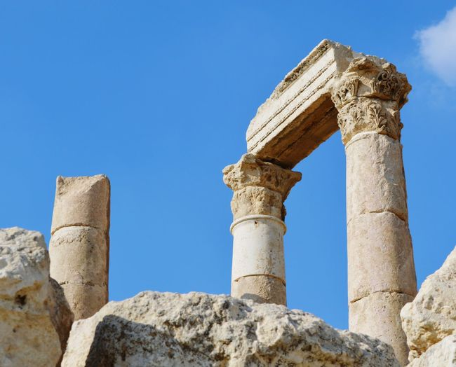 Low angle view of ruins at amman citadel against blue sky