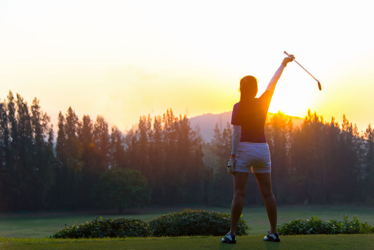 Rear view of woman standing on golf course against sky during sunset