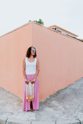 Woman standing against pink wall against sky
