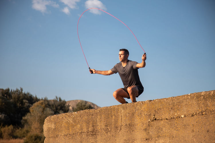 Low angle view of young man jumping against clear sky