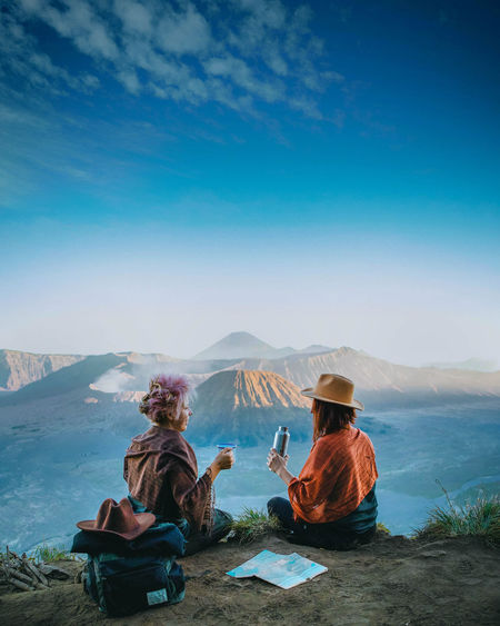 Sitting Mountain Sky Real People Leisure Activity Beauty In Nature Nature Scenics - Nature Mountain Range Relaxation People Tranquility Two People Day Environment Outdoors Looking At View Volcano Nature Nature Photography INDONESIA Drink Travel Destinations Travel Travel Photography Exploring Fun