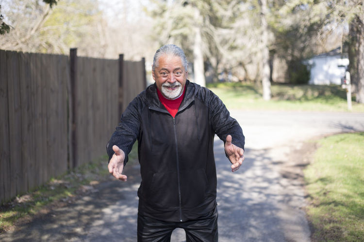 Portrait Of Smiling Senior Man Gesturing While Standing On Footpath At Park