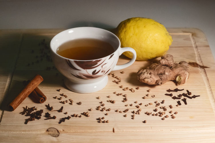 High angle view of herbal tea by spices and lemon on cutting board
