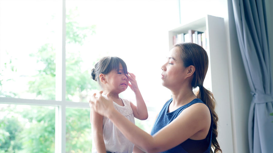 Woman consoling daughter crying at home