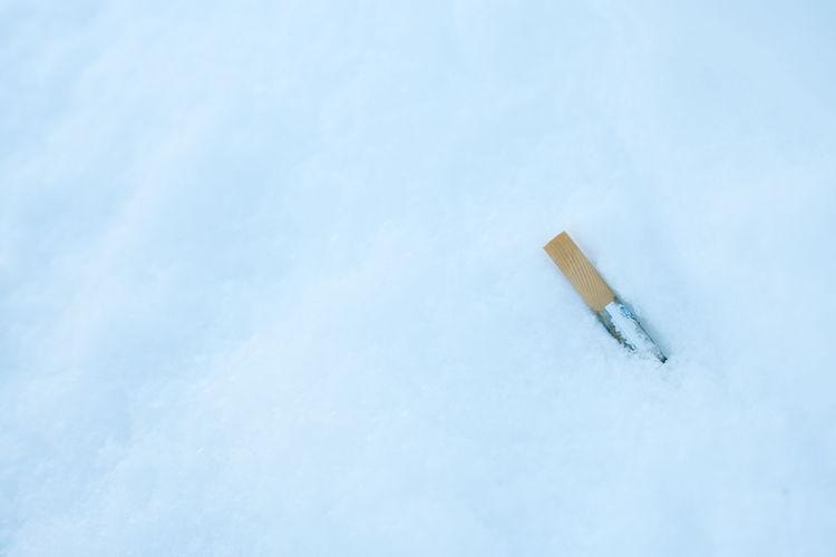 Close-up of cigarette smoking on snow