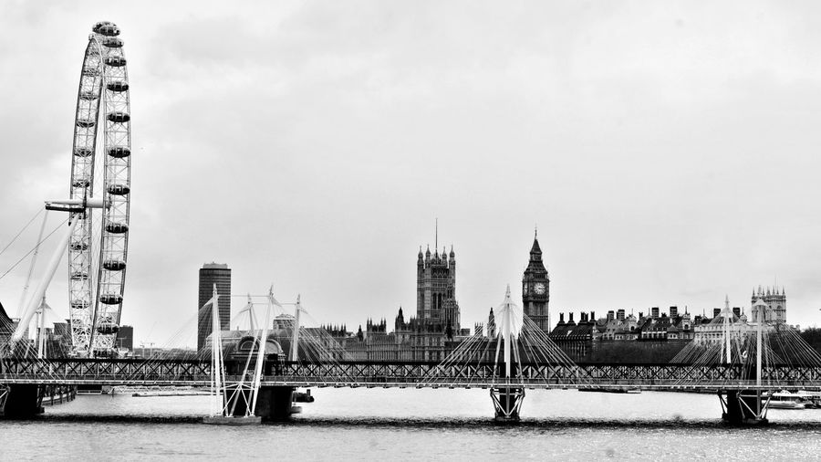 View of ferris wheel and big ben in city against sky