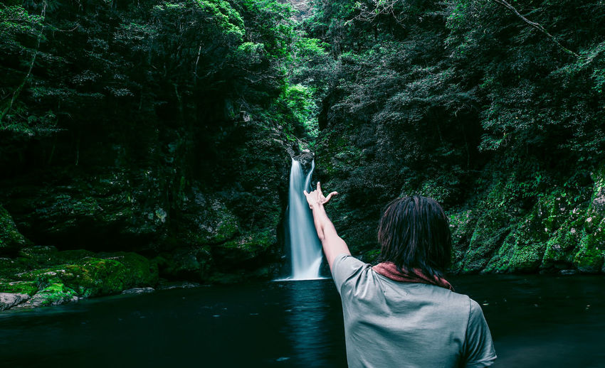Rear View Of Man Doing Hand Sign Against Waterfall