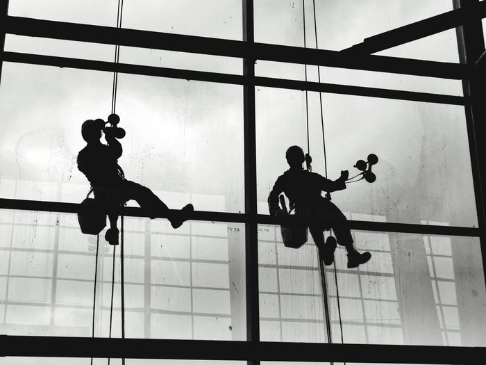 Low angle view of silhouette men on glass window