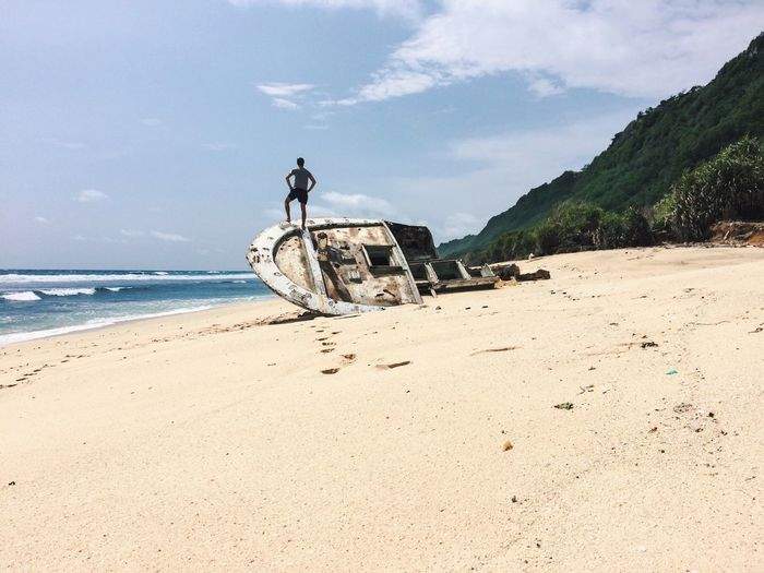 Man Standing On Shipwreck At Beach Against Sky