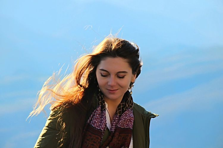 Low angle view of beautiful woman with tousled hair against sky