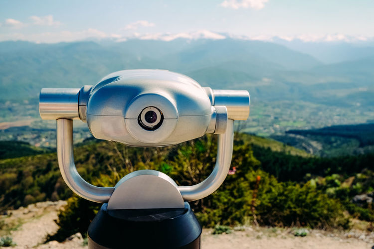 Coin-Operated Binocular Against Mountains