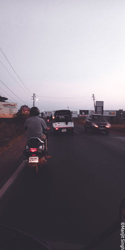 Rear view of vehicles on road at sunset