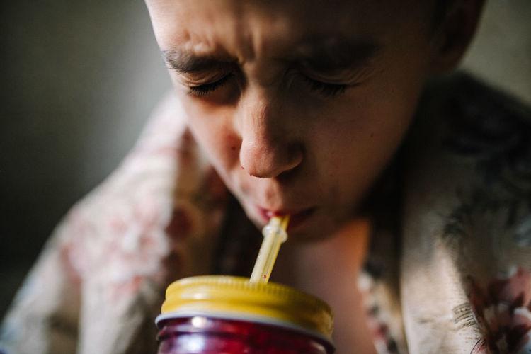 Close-up of boy drinking juice