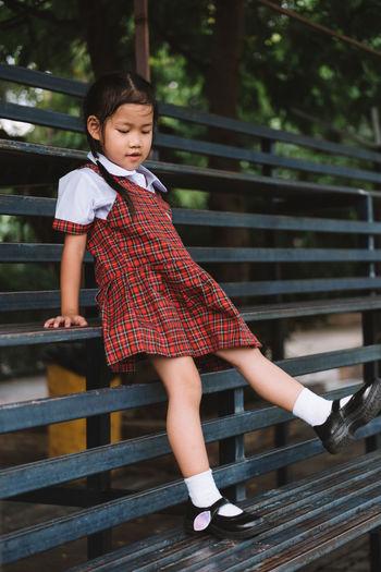 Full Length Of Girl In School Uniform Sitting On Bench