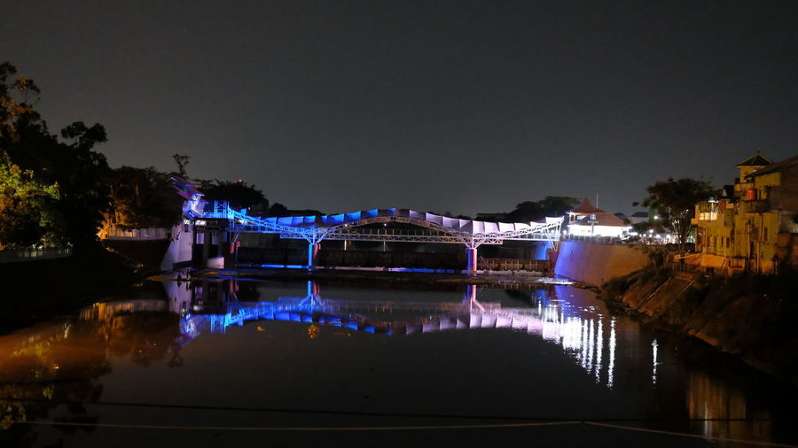 Illuminated bridge over river in city against clear sky at night