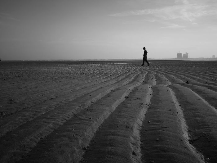 Silhouette man standing on beach against sky
