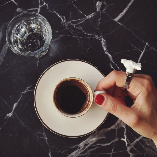 Cropped Image Of Woman Hand Holding Coffee Cup On Table