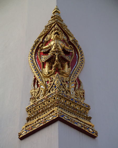Low angle view of gold demon sculpture on wall