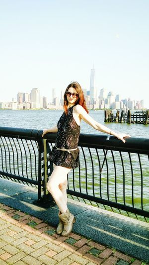 Beautiful Woman Posing While Standing By Railing At Riverbank