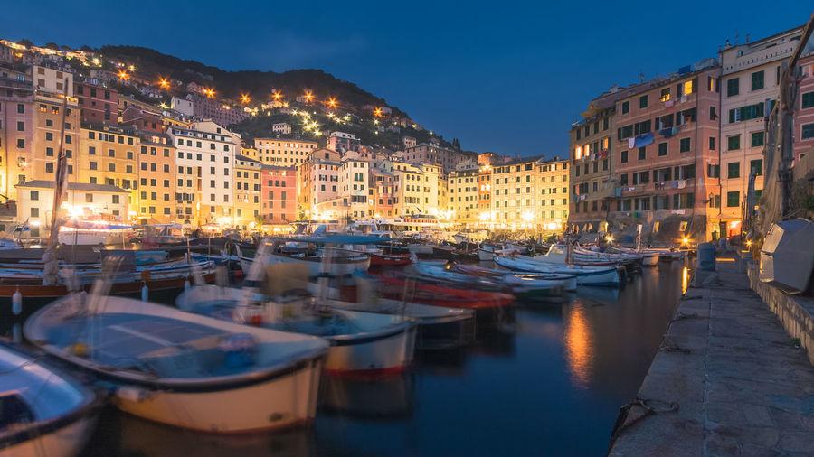 Boats moored in illuminated city at night