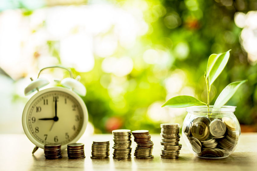The concept of saving money for the future and building financial stability and sustainable living and hand putting money coin and tree growing in jar. Wealth Finance Coin Nature Business Clock Alarm Clock No People Investment Focus On Foreground Currency Plant Table Savings Still Life Time Close-up Green Color Copy Space Large Group Of Objects Economy Clock Face