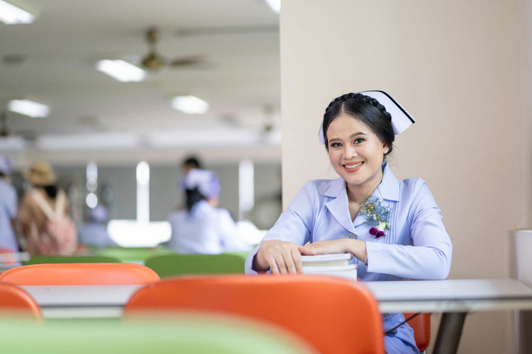 nurse Looking At Camera Indoors  Young Adult Education Happiness Women Front View Table Portrait Learning Sitting Young Women One Person Smiling Adult Book Emotion Furniture Seat Hairstyle Nurse Library Nursing Student Nursing White Uniform Beautiful Woman The Portraitist - 2019 EyeEm Awards