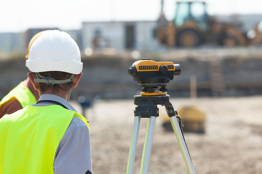Land surveying. Construction site worker. Working Construction Site Earth Mover Fieldwork Geodesist Geodesy Geometer Geometry Helmet Industry Land Surveying Land Surveyor Measure Occupation Outdoors Protective Workwear Theodolite Working