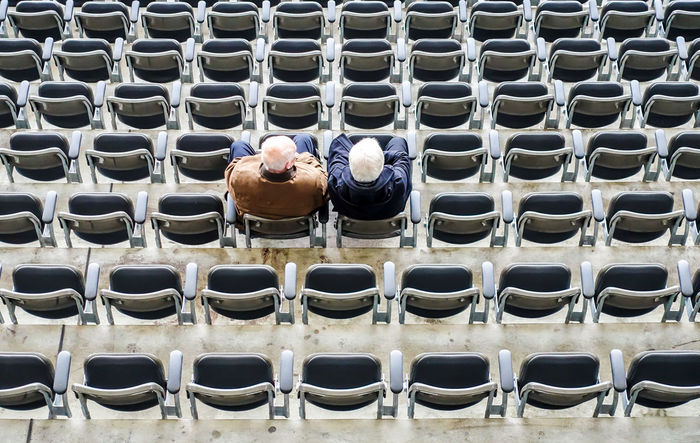 High angle view of friends sitting on chairs at stadium