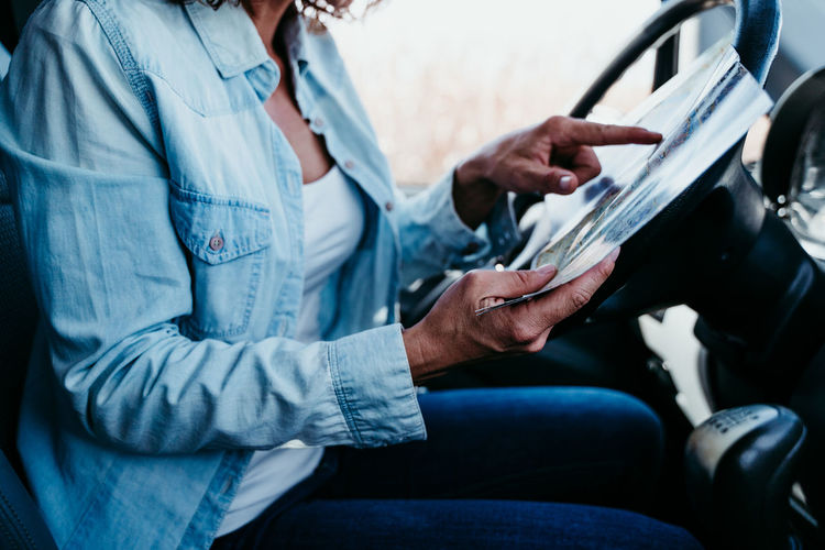 Midsection of woman analyzing map in camper trailer