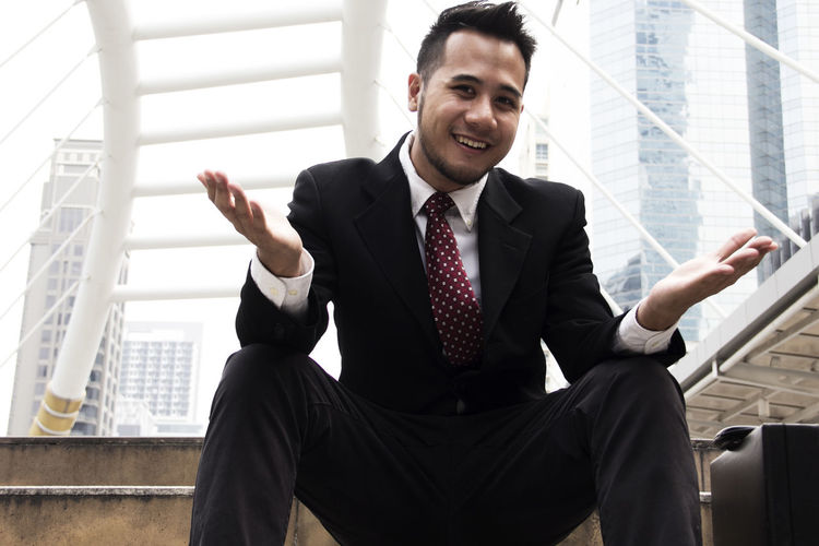 Portrait of smiling mid adult man sitting in office