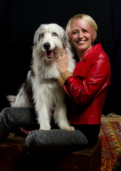 Adult Animal Themes Black Background Blond Hair Day Dog Domestic Animals Front View Happiness Indoors  Looking At Camera Mammal Mature Women One Animal One Person People Pets Portrait Real People Sitting Smiling Young Adult Young Women