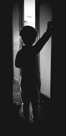 Rear view of silhouette boy standing against wall at home
