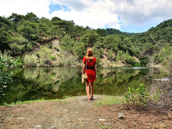 Rear view of woman standing by lake against sky /  woman in red dress / green landscape