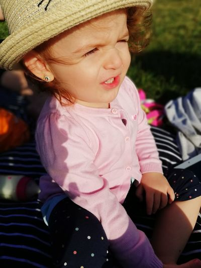 High Angle View Of Cute Baby Girl Wearing Hat Sitting In Park During Sunny Day