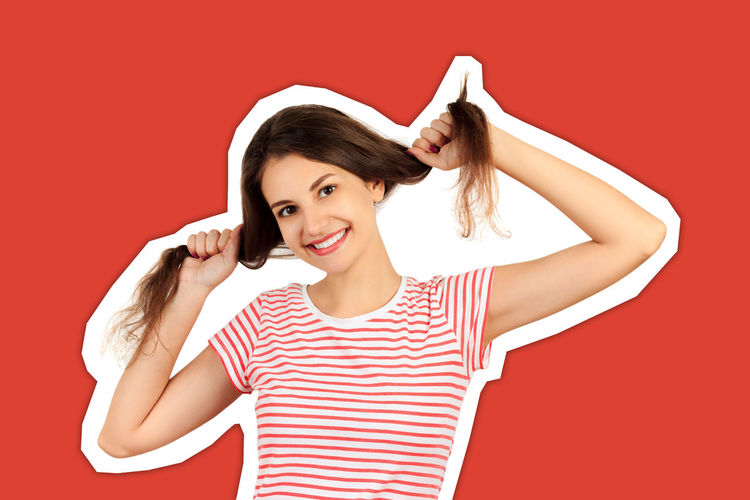 Portrait of a smiling young woman against red background