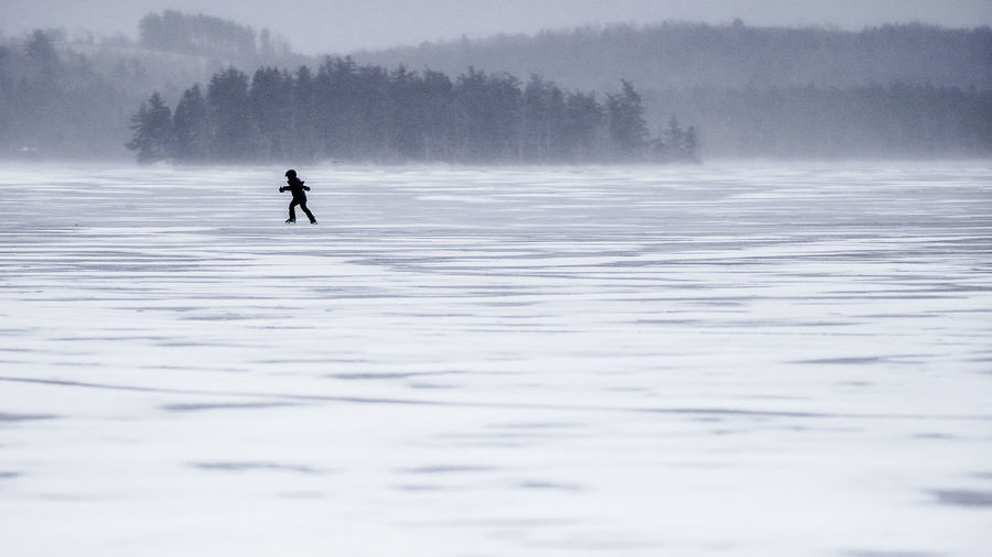 Distant View Of Silhouette Boy Ice Skating On Frozen Lake