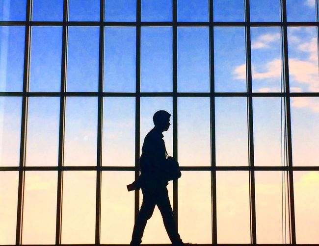 Silhouette man walking against window