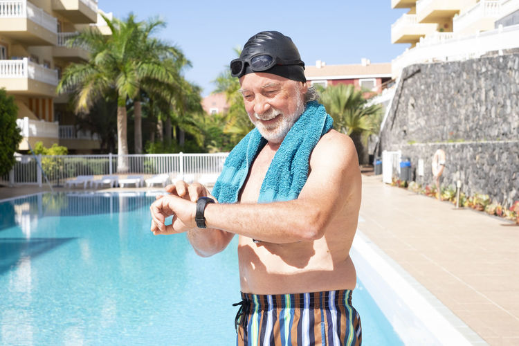 Smiling man checking time while standing by swimming pool