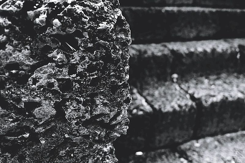 Close-up of stone wall with steps in background