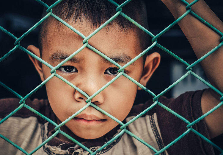 ASIA Alone Cry Imprisoned Barrier Boundary Chainlink Fence Close-up Fence Front View Headshot Human Face Leisure Activity Lifestyles Looking At Camera Metal One Person Portrait Protection Real People Sad Sadness Safety Security Young Adult