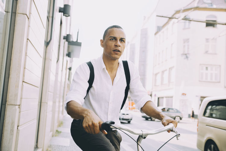 Portrait of man standing by bicycle
