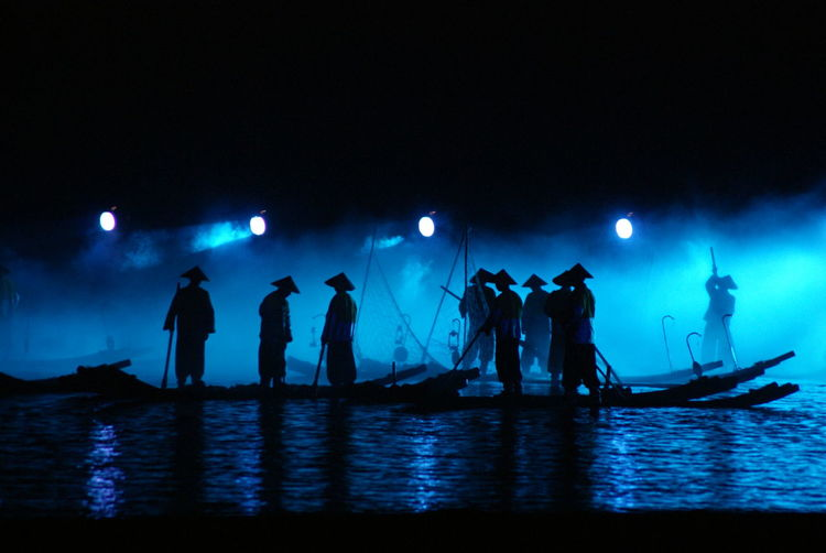 Silhouette men standing on boat in lake at night