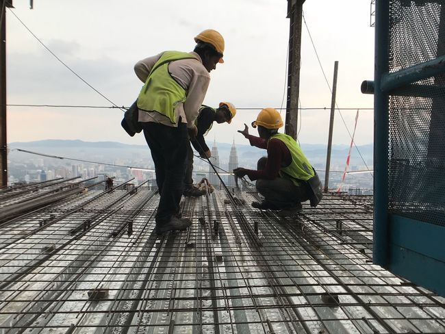 Man at work at High rise building tower in Kuala Lumpur Tower Buildings High Rise Buildings Headwear Reflective Clothing Protective Workwear Industry Occupation Hardhat  Safety Men Working Helmet Protection Real People Engineer Only Men Day Full Length Manual Worker Outdoors Teamwork