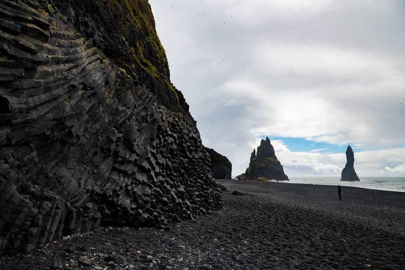 Black sand beach and the basalt mount Reynisfjall, Vik,Iceland. Iceland Beach Beauty In Nature Black Black Sand Beach Cliff Formation Geology Icelandic Land Landmark Lava Mountain Nature Outdoors Rock Rock - Object Rock Formation Sand Scenics - Nature Sea Sky Volcanic Landscape Volcano