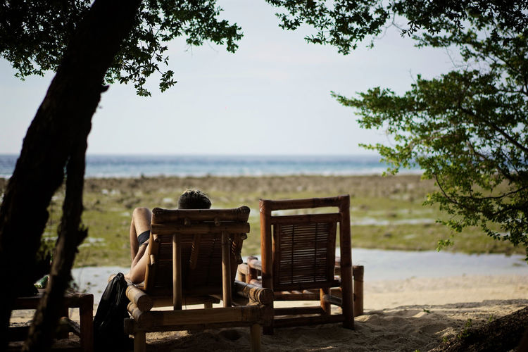 Beach Bench Day Land Leisure Activity Men Nature One Person Outdoors Plant Real People Relaxation Sea Seat Sitting Sky Transportation Tree Water