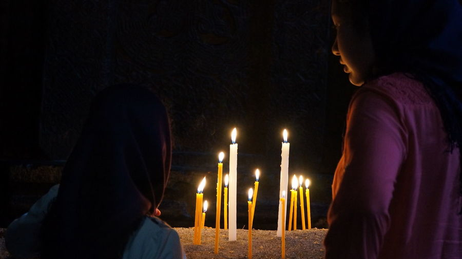 Rear view of women on illuminated candles