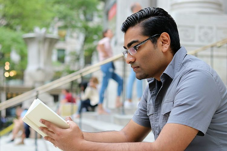 Young man reading book while sitting on steps in city