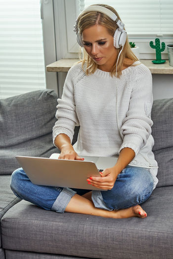 One Person Sofa Sitting Hair Blond Hair Casual Clothing Women Young Women Furniture Indoors  Lifestyles Home Interior Real People Front View Young Adult Technology Communication Adult Holding Wireless Technology Hairstyle Jeans Using Laptop Surfing The Net