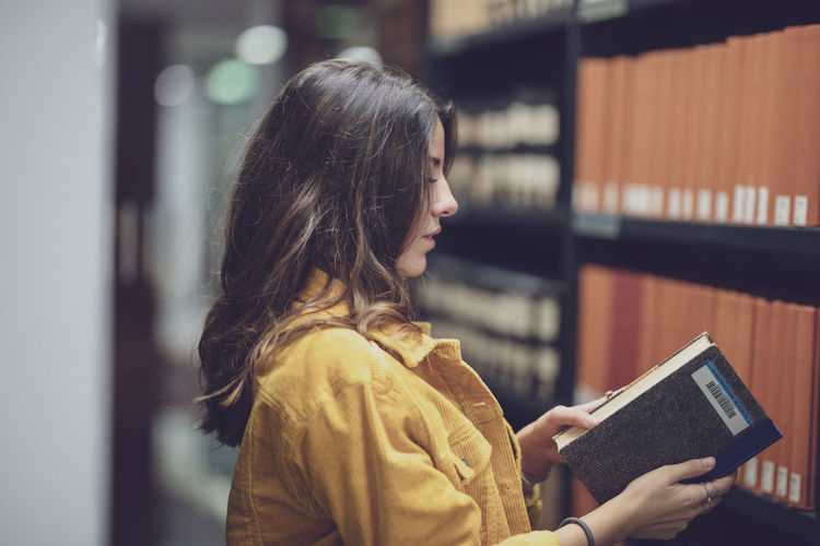 Side view of young woman holding book at library