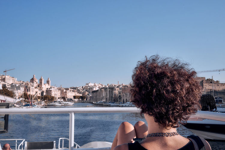 Rear view of woman looking at cityscape against clear sky